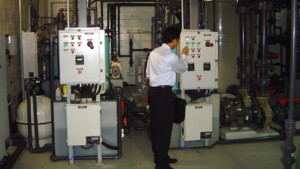 The author inspects a filtration system control panel public aquarium built and managed by Issham Aquatics. Photo by Isshamaqua.com