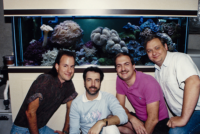 Left to right: Julian Sprung, Charles Delbeek, Mike Paletta, and John Burlseon in front of John's reef tank, 1990.
