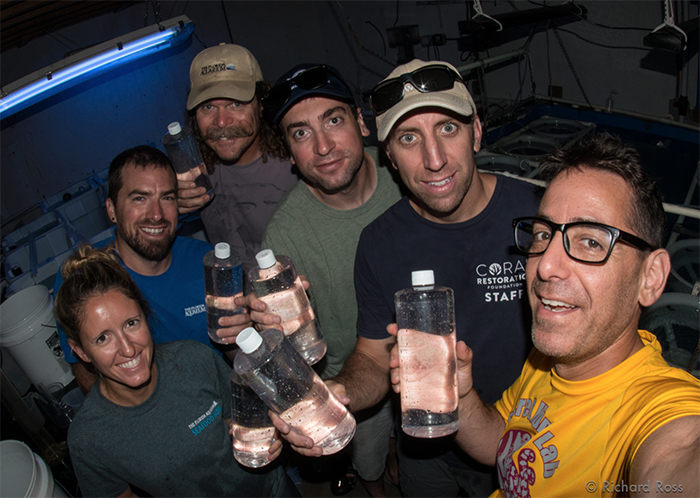 Happy people holding bottles containing thousands of swimming baby corals. Photo by Rich Ross.
